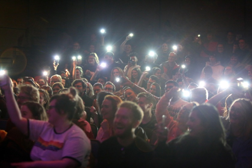 Audience in darkened room hold phones with lights aloft like lighters