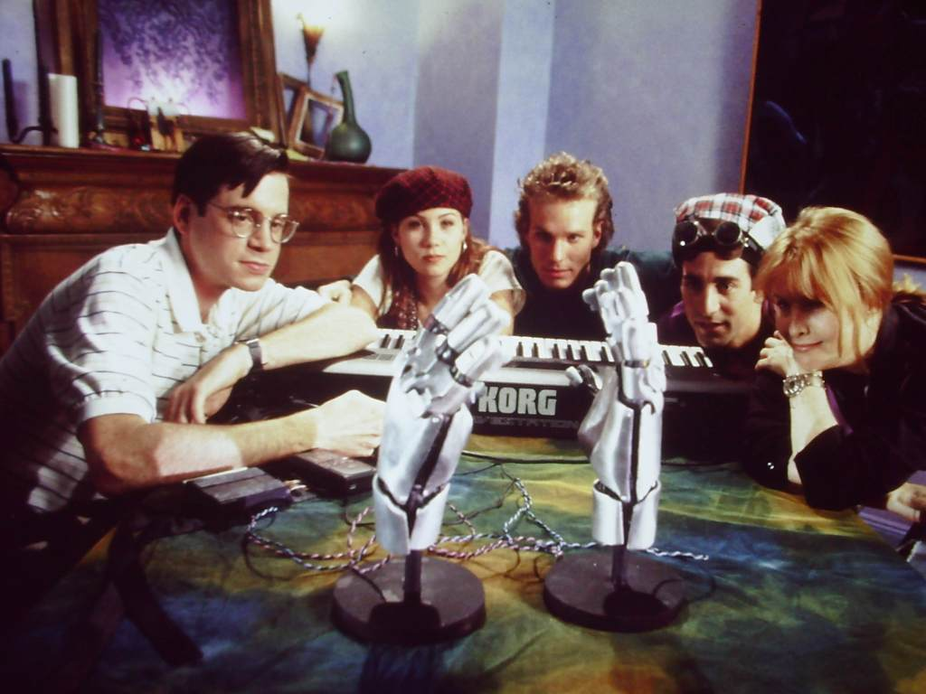 Five young people gather around a table, with musical equipment and random tech strewn on it, staring at a pair of metallic hands.