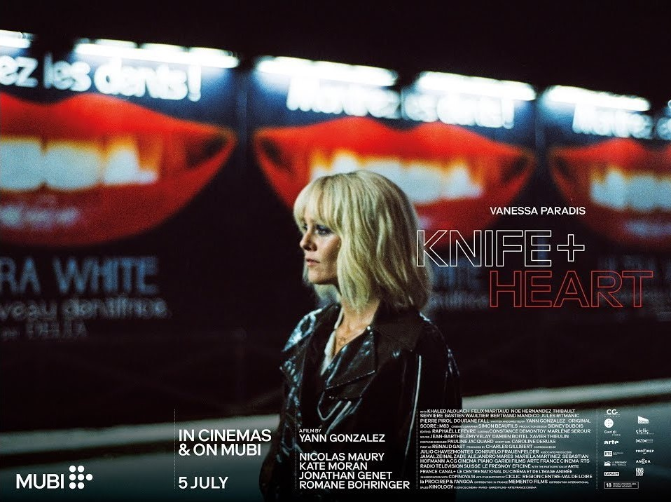 Quad poster for Knife + Heart, woman with bleach blonde hair and leather jacket (Vanessa Paradis) stands in front of blurry billboard adverts
