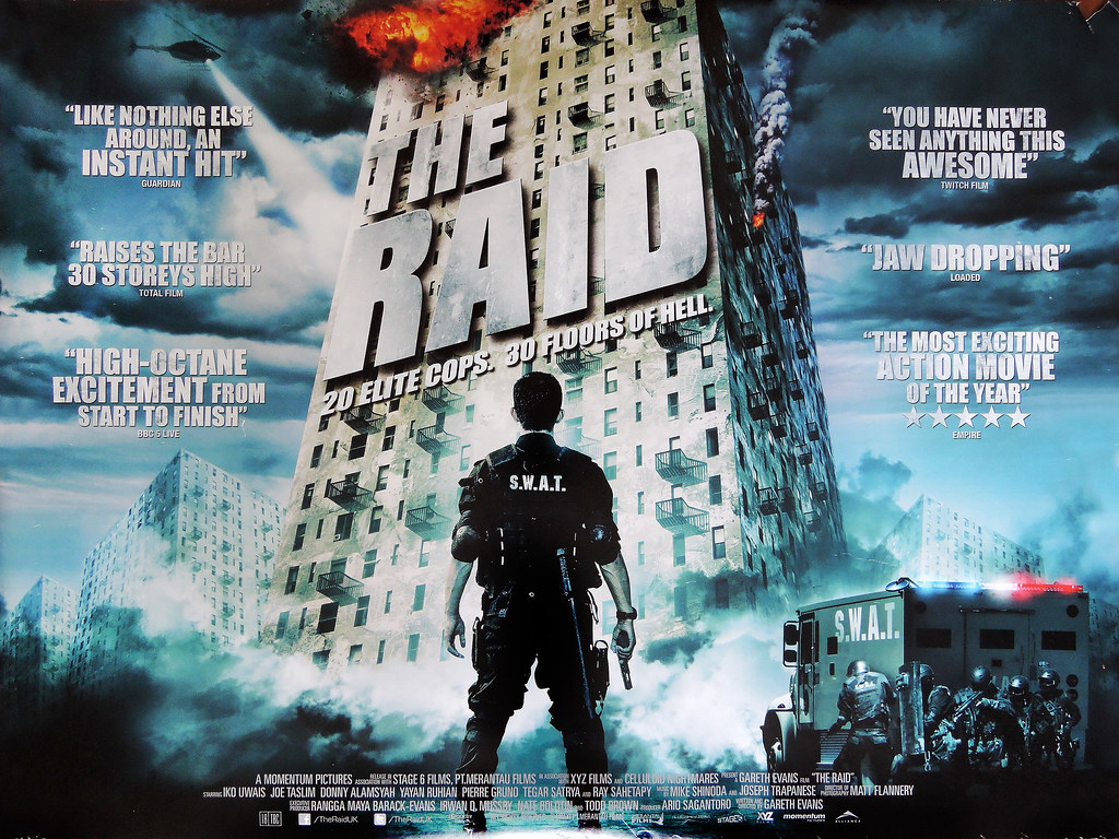 Quad poster for The Raid. A SWAT police officer stands back to camera facing a tower block, with the film's name in giant letters