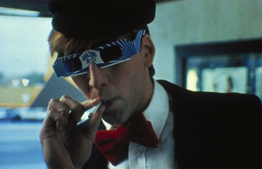 Nicolas Cage as Randy in Valley Girl, wearing 3D glasses and smoking a cigarette